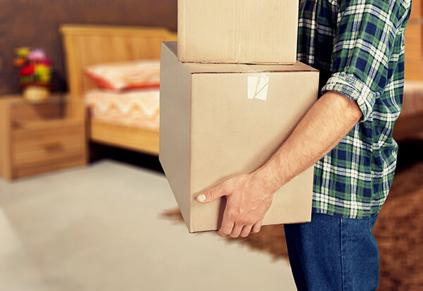 Image of man carrying domestic storage boxes