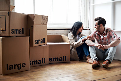 Homeowners sitting in empty house with boxes stacked next to them